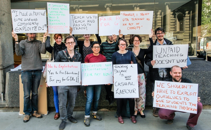 Kings Graduate Teaching Assistants holding placards protesting exploitation